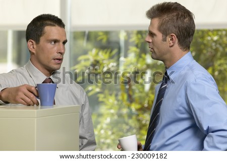 Portrait of two young businessmen socializing at the water cooler - stock photo