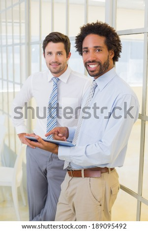 Portrait of two young businessmen with digital tablet standing in the office