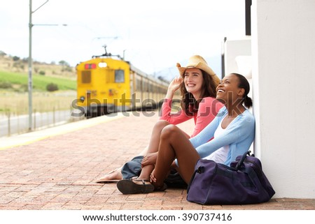 Portrait of two young female friends sitting at railroad station and waiting for train - stock photo