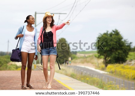 Portrait of two young female friends walking along a railroad station and looking at a view - stock photo