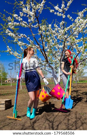 Portrait of two young females with rakes and spade on garden  - stock photo