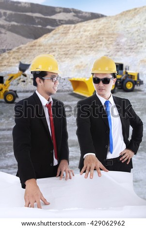 Portrait of two young foremen discussing at the mining sites while looking at the blueprint - stock photo