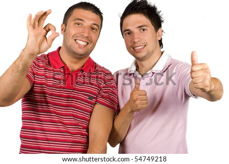 Portrait of two young friends giving okay sign and thumb up isolated on white background - stock photo
