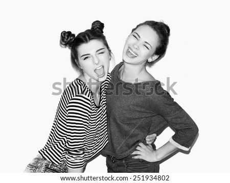 Portrait of two young girl having fun and laughing. One hugging other. Top knot hairdo. White background, not isolated. Inside - stock photo