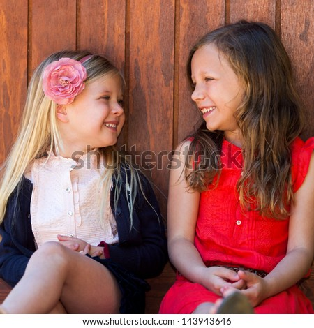 Portrait of two young girls laughing together outdoors. - stock photo