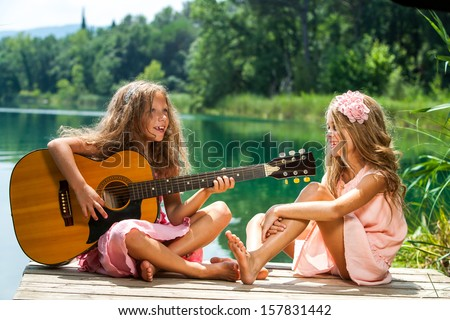 Portrait of two young girls singing together at lakeside. - stock photo