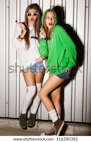 Portrait of two young good looking girls sucking lollipops, outdoors - stock photo