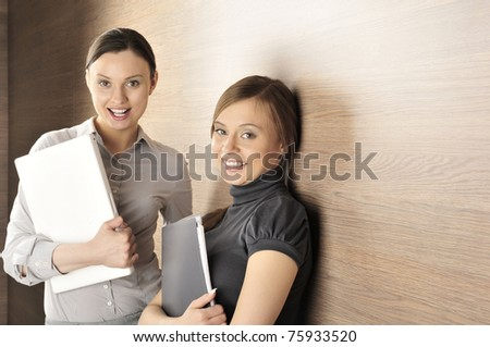 Portrait of two young handsome women standing relaxed against modern wooden wall in their office smiling and holding laptop and folder with papers