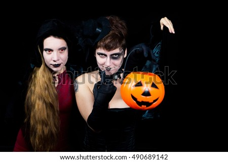 Portrait of two young make up women holding pumpkins, isolated on black. Halloween and body art concept.