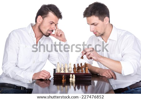 Portrait of two young man are playing chess on the white background. - stock photo