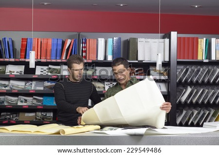 Portrait of two young men looking at blueprints in office setting - stock photo