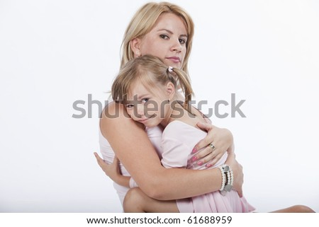 Portrait of two, young mother and daughter, hugging close, studio image