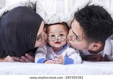 Portrait of two young muslim parents lying on the bed while kissing their baby under the blanket - stock photo