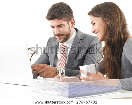 Portrait of two young professionals sitting in front of computer and consulting. Business people working together on next project. Isolated on white background.  - stock photo