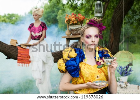 Portrait of two young romantic women on a picnic in a fairy forest. Outdoors. - stock photo