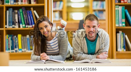 Portrait of two young students with books lying on the library floor