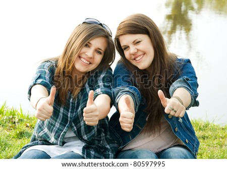 Portrait of two young teenagers laughing and giving the thumbs-up sign