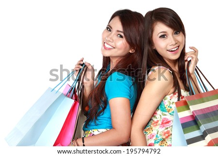 Portrait of two young woman happy holding shopping bags, isolated over white background - stock photo