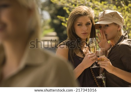Portrait of two young women gossiping with a woman in the foreground