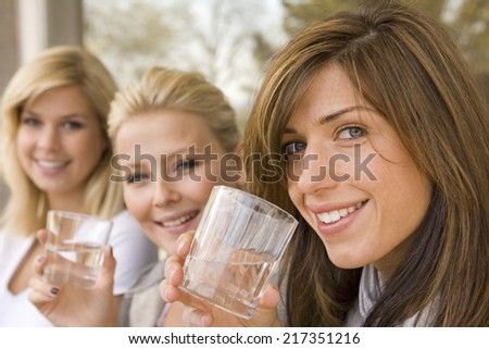 Portrait of two young women holding glasses of wine with their friend smiling in the background - stock photo