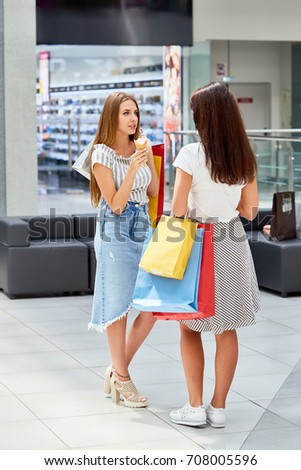 Portrait of two young women shopping in mall, taking a break to chat in hall holding paper bags and eating ice cream cones