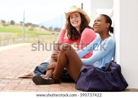 Portrait of two young women sitting at railroad station and waiting for train - stock photo