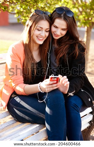 Portrait Of Two Young Women Sitting On Bench Sharing Headphones And Listening Music - stock photo