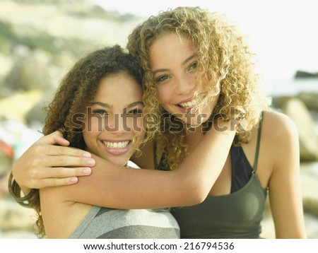 Portrait of two young women smiling with their arms around each other