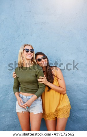 Portrait of two young women standing together over blue background. Stylish young female models looking away and smiling. - stock photo