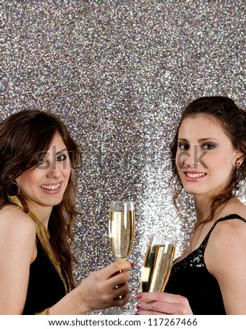 Portrait of two young women toasting with champagne glasses at a Christmas party with a silver glitter background.