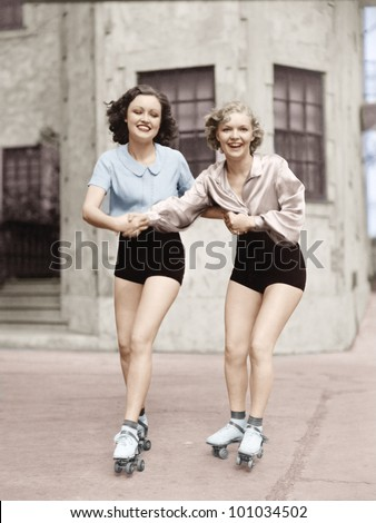 Portrait of two young women with roller blades skating on the road and smiling - stock photo