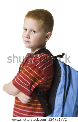 Portrait of unhappy boy standing with school bag