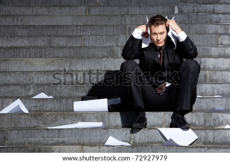 Portrait of unhappy businessman under depression touching his head in grief - stock photo