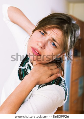 Portrait of unhappy female with neck and shoulders aching