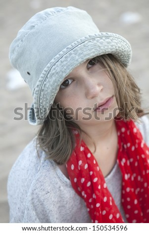portrait of Unhappy little girl in hat and red scarf in spot - stock photo