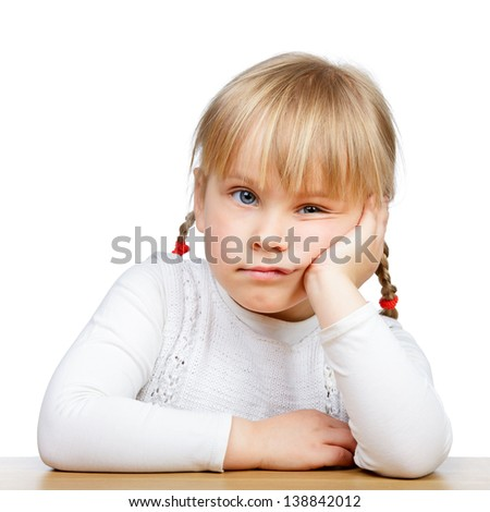 Portrait of unhappy little girl sitting at desk with hand on chin - stock photo