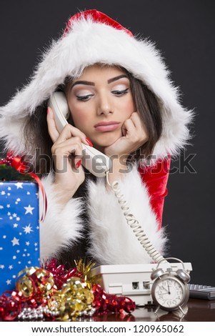 Portrait of unhappy Santa girl speaking on the phone with alarm clock, gift box and decorations on desk.
