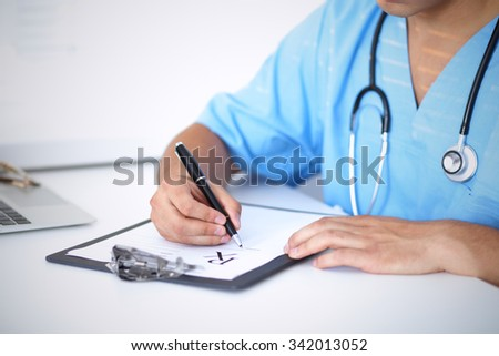 Portrait of unknown male surgeon doctor holding his stethoscope and filling up medical prescription