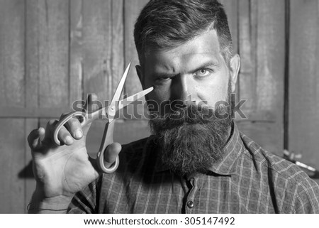 Portrait of unshaven boy in checkered shirt with long beard and handlebar moustache showing sharp scissors looking forward standing on wooden wall background black and white, horizontal picture - stock photo