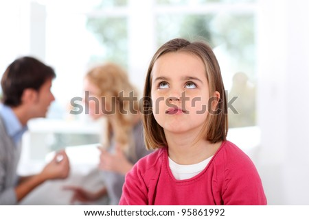 Portrait of upset child with parent's fighting - stock photo