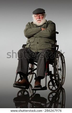 Portrait of upset elderly man sitting on a wheelchair with his arms crossed over grey background - stock photo