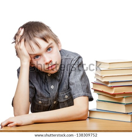 Portrait of upset schoolboy sitting at desk with books holding his head - stock photo