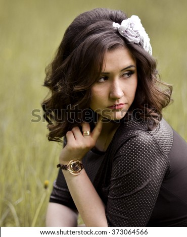 Portrait of upset,unhappy,sorrowful,beautiful,attractive,pretty,nice girl,woman,model with wreath in the curly,brown,shiny,short hair,sitting in the park,thinking about something,worry about problems. - stock photo