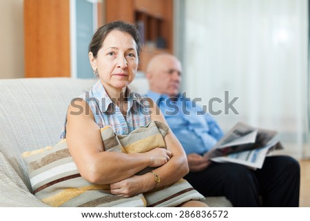 Portrait of upset woman near elderly man with newspaper at home - stock photo