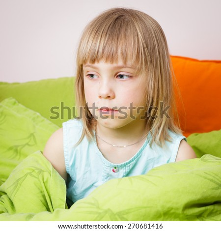Portrait of upset 6 year old blond girl sitting in her bed with a chickenpox rash on her face - stock photo