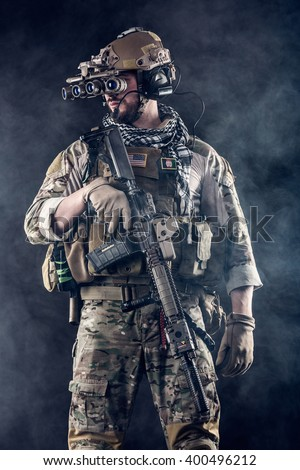Portrait of US Army Soldier with Foue-eyed night vision goggles in the Smoke; Dark Background - stock photo
