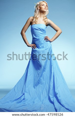 Portrait of very beautiful woman wearing long dress over blue - stock photo