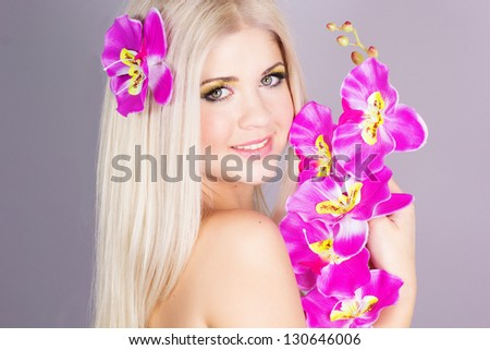 Portrait of very beautiful woman with orchid - stock photo