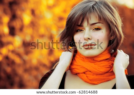 Portrait of very beautiful young woman in autumn park - stock photo