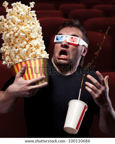 Portrait of very scared man watching 3D movie, drinking cola and eating popcorn - stock photo